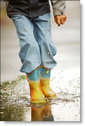 Boy splashing in the rain puddles